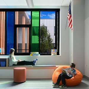 kids sitting and reading by a colorful window under an American flag